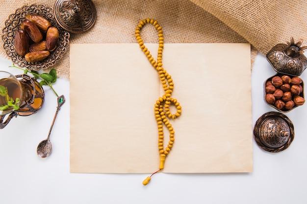 Dattelfrucht mit perlen und leerem papier