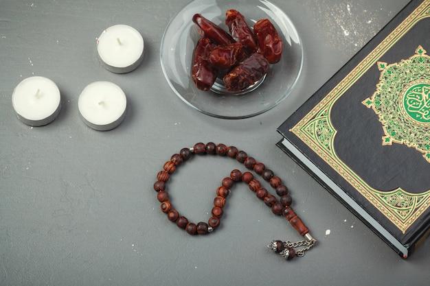 Dattelfrüchte, koran und hölzerne rosenkranzperlen auf dem hölzernen für moslems ramadan, gesegnete freitag-mitteilung und drei monate konzept