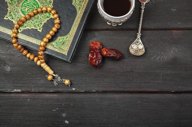 Dattelfrüchte, koran und hölzerne rosenkranzperlen auf den hölzernen moslems ramadan, gesegnete freitagsbotschaft und drei monate