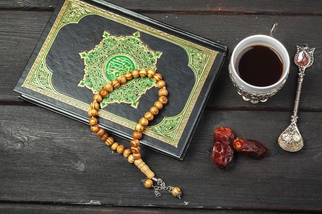 Dattelfrüchte, koran und hölzerne rosenkranzperlen für moslems ramadan, gesegnete freitag-mitteilung und drei monate konzept