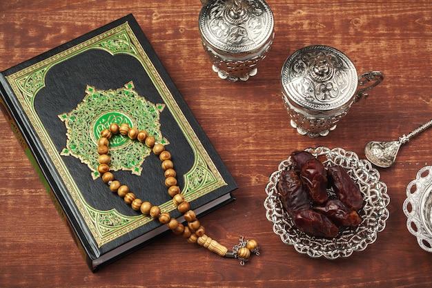 Dattelfrüchte, koran und holzoberflächenrosenkranz auf der holzoberfläche für moslems ramadan