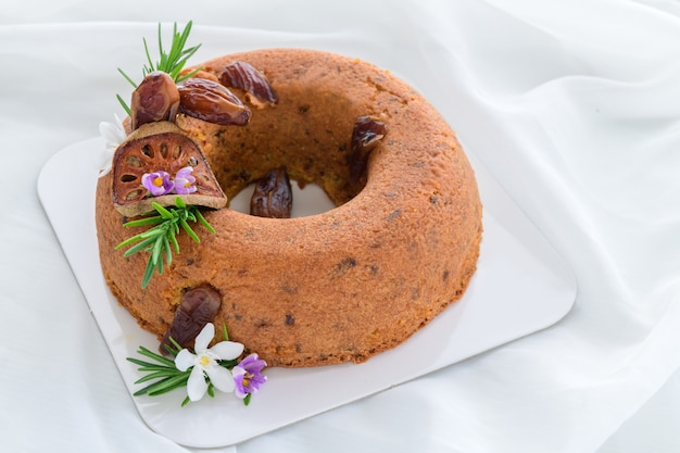 Dattelkuchen und mit getrockneten datteln dekorieren. getrocknete quitten- und rosmarinblätter auf weißer stoffoberfläche, gesundes kuchenkonzept
