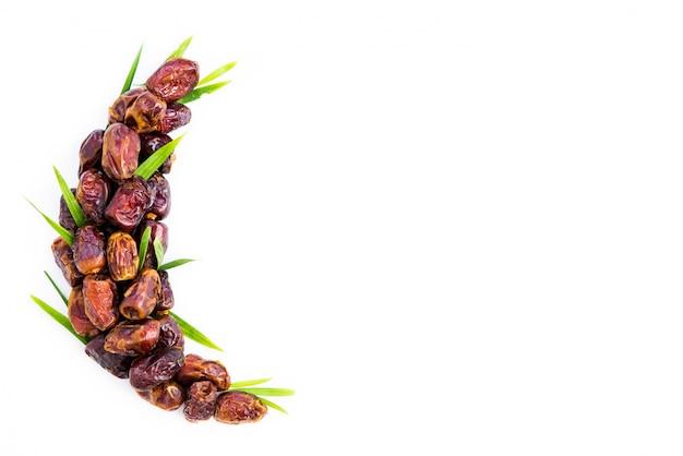 Datteln palmenfrucht angeordnet in form des halbmondes. ramadan kareem.