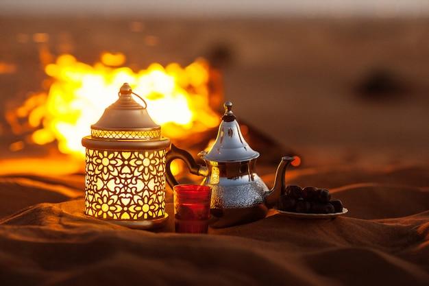 Datteln, teekanne, tasse mit tee in der nähe des feuers in der wüste mit einem schönen hintergrund. ramadan kareem