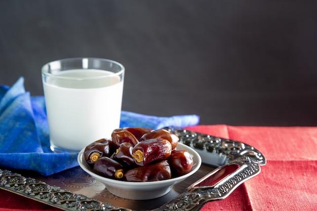 Datteln und ein glas milch auf metalltablett - ramadan, iftar essen.