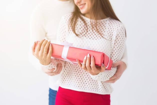 Datum valentinstag und geburtstag konzept nahaufnahme von mann und frau hält box mit geschenk auf weiß