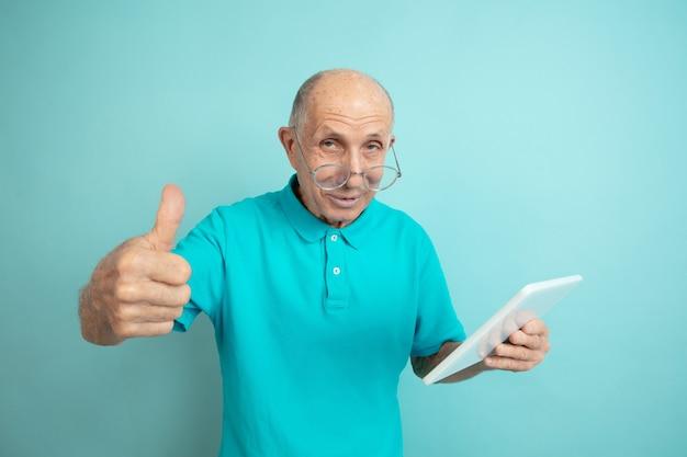 Daumen hoch mit dem tablet. porträt des kaukasischen älteren mannes auf blauem studiohintergrund. schönes männliches emotionales modell. konzept der menschlichen emotionen, gesichtsausdruck, verkauf, wohlbefinden, anzeige. copyspace.