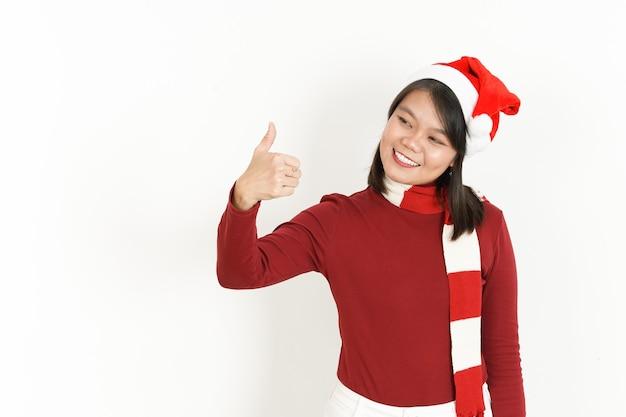 Daumen hoch ok zeichen der schönen asiatischen frau mit rotem rollkragenpullover und weihnachtsmütze isoliert auf weiss