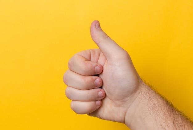 Daumen hoch verletzt oder schlechter fingernagel auf gelbem hintergrund. schließen sie oben daumen mit schlechter maniküre nahaufnahme