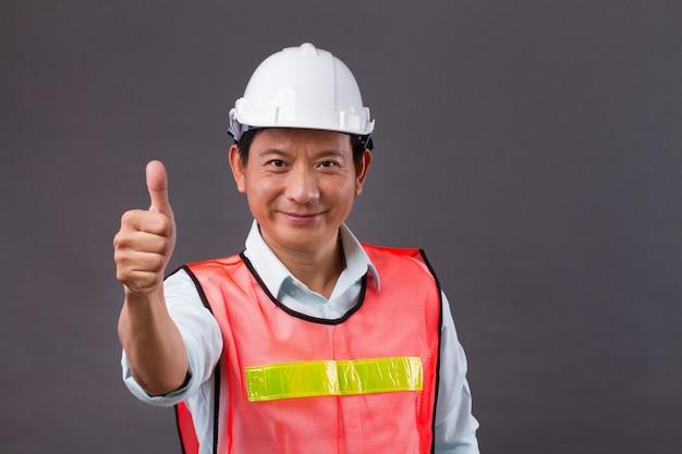 Daumen hoch von selbstbewusstem, professionellem asiatischen ingenieur, bauingenieur, bauunternehmer, architekt, arbeiter
