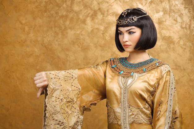 Daumen runter mögen keine geste. glamouröses nahaufnahmeporträt des schönen sexy stilvollen brünetten jungen frauenmodells mit hellem make-up. kleopatra