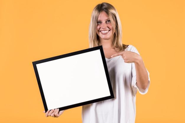 Deaktivieren sie die jungen blondine, die finger auf leeren weißen bilderrahmen zeigen