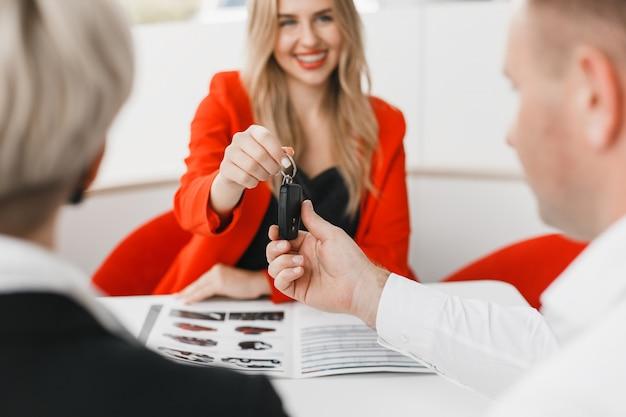 Deal zum verkauf auto ist vorbei. paar nimmt einen schlüssel.