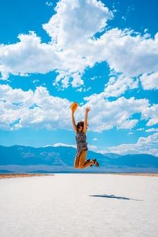 Death valley, kalifornien vereinigte staaten. eine junge frau, die mit einem blauen hemd auf dem weißen salz des badwater basin springt