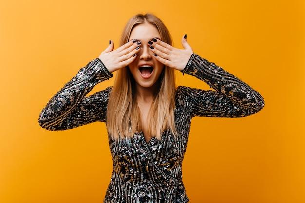 Debinair weiße frau mit trendiger maniküre, die ihre augen bedeckt. innenporträt der lachenden aufgeregten frau, die auf orange steht.