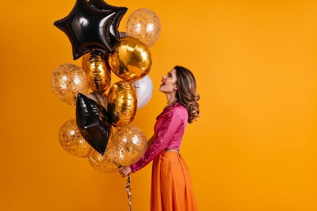 Debonair frau, die partyballons betrachtet