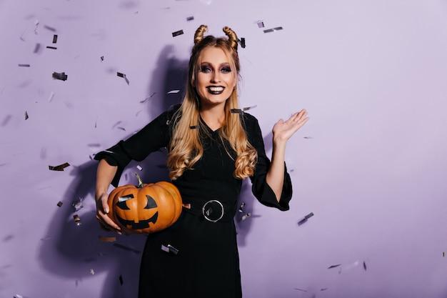 Debonair junge frau mit gruseligem make-up, das im halloween-karneval entspannt. lachendes langhaariges mädchen in vampirkleidung, die auf der party mit kürbis aufwirft.