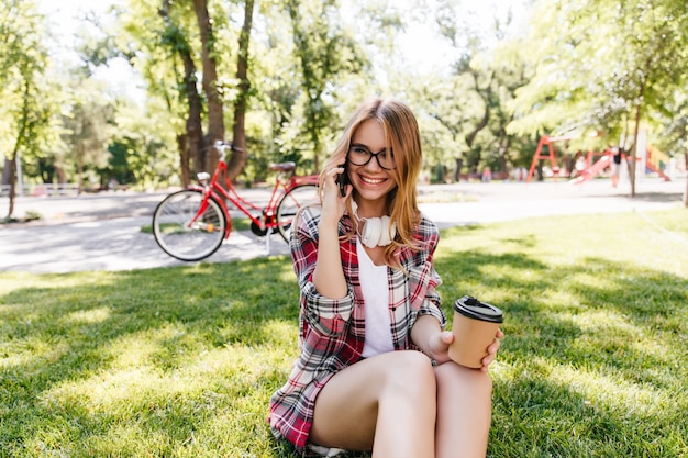 Debonair-mädchen, das am telefon spricht, während auf gras sitzt. außenfoto der lächelnden liebenswerten frau mit tasse kaffee.