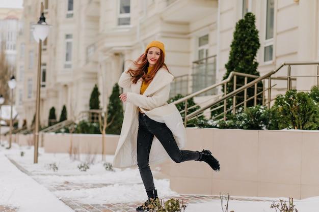 Debonair-mädchen im weißen kittel, der im wintertag springt. foto im freien der verträumten frau, die kaltes wetter genießt.