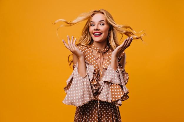 Debonair weibliches modell in der weinlesebluse, die erstaunen ausdrückt. innenfoto des positiven mädchens, das mit überraschtem lächeln auf gelber wand aufwirft.