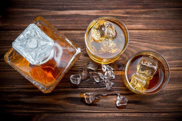 Decander und zwei gläser mit eis und whisky