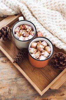 Decke in der Nähe von Tablett mit heißer Schokolade und Zapfen