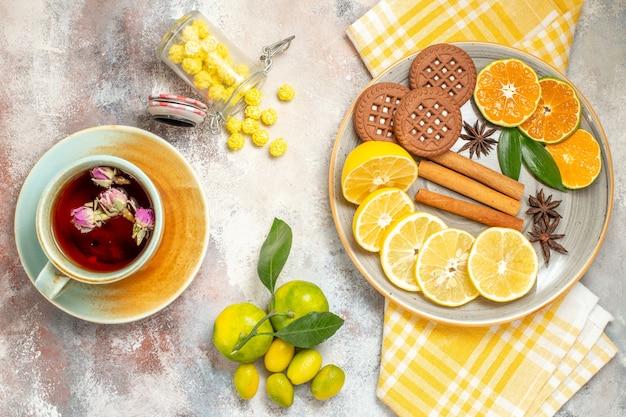 Decken sie den tisch für kaffee und tee mit einer tasse tee, keksen und zitronenscheiben auf einem weißen tisch
