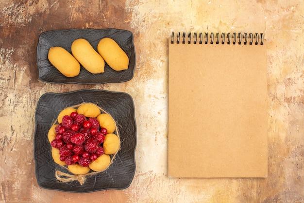 Decken sie den tisch mit einem geschenkkuchen für gäste und ein notizbuch auf einem tisch mit gemischten farben