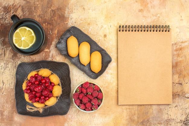 Decken sie den tisch mit einem geschenkkuchen und einer tasse tee mit zitrone und notizbuch auf einem tisch mit gemischten farben