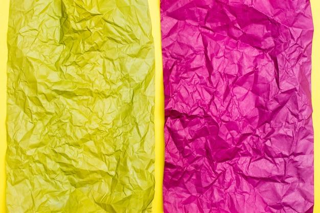 Decken sie zerknittertes purpurrotes und gelbes blatt farbiges papier auf einem gelben papphintergrund ab. struktureller bunter hintergrund. ansicht von oben. kopieren sie platz