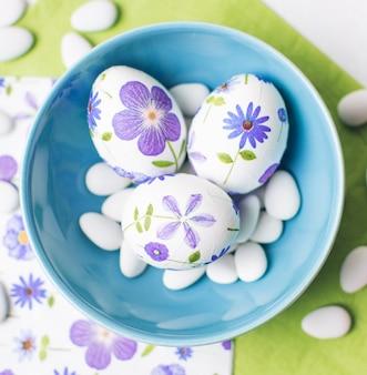 Decoupagierte eier mit dragees in schüssel