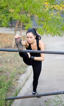 Dedictaed sportlerin streckte ihre muskeln mit hoch erhobenem fuß auf einer metallstange und ihr gewicht verlagerte sich nach vorne