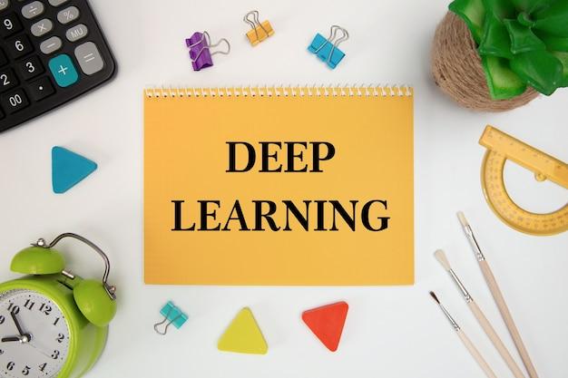 Deep learning wird in ein notizbuch auf einem bürotisch mit büromaterial geschrieben