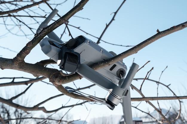Defekte kardanische kamera und drohnenmotorarm nach crash auf baumzweig-nahaufnahme