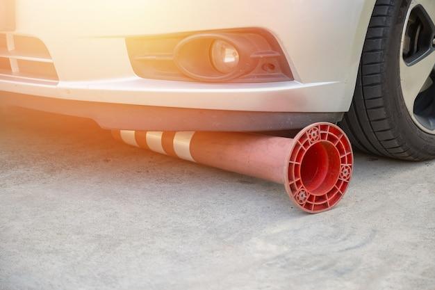 Defekter flexibler verkehrspoller unter dem auto auf der straße