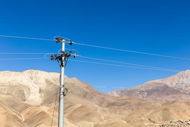 Defekter isolator auf einem freileitungsmast in den bergen