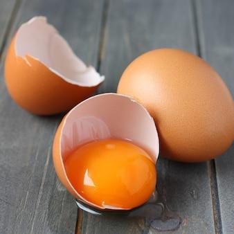 Defektes frisches ei auf rustikalem hölzernem hintergrund