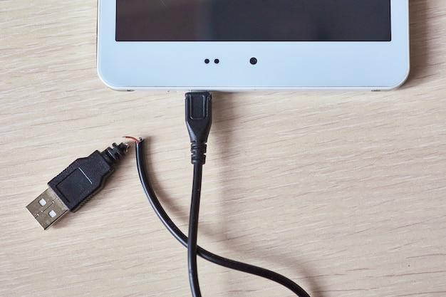 Defektes usb-kabel auf holztisch