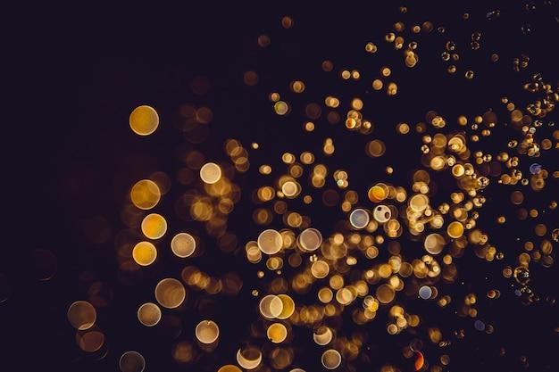 Defocus-bokeh funkelngoldweinlese beleuchtet dunklen hintergrund