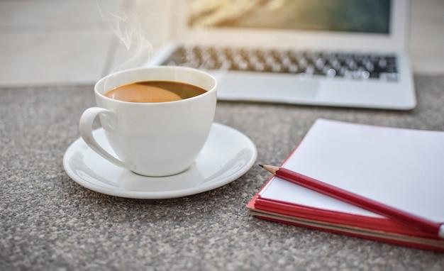 Defocus kaffeetasse auf boden mit notizbuch und laptop, morgen, heißer kaffee