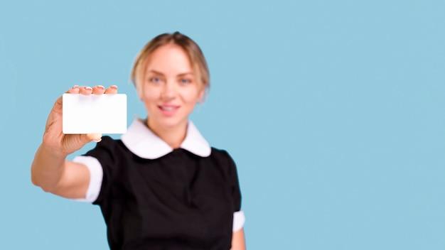 Defocused frau, die unbelegte weiße visitenkarte vor blauem hintergrund zeigt