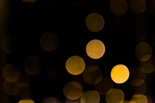 Defocused glühendes licht des weihnachtsauszuges auf dunklem hintergrund