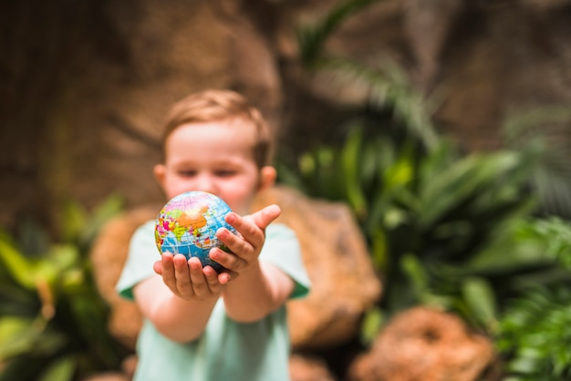 Defocused junge, der kugelball in seiner hand hält