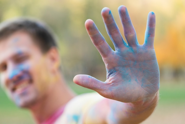Defocused mann, der blaue hand am festival zeigt