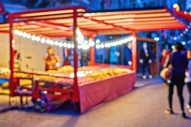 Defocused menge von leuten während des weihnachtsmarkts eine alte stadtstraße mit bunten weihnachtslichtern