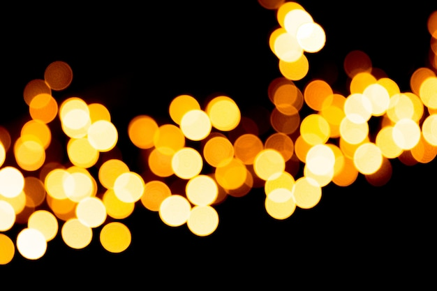 Defocused stadtgoldnacht-bokeh zusammenfassungshintergrund. verschwommen viele runde gelbes licht auf dunklem hintergrund