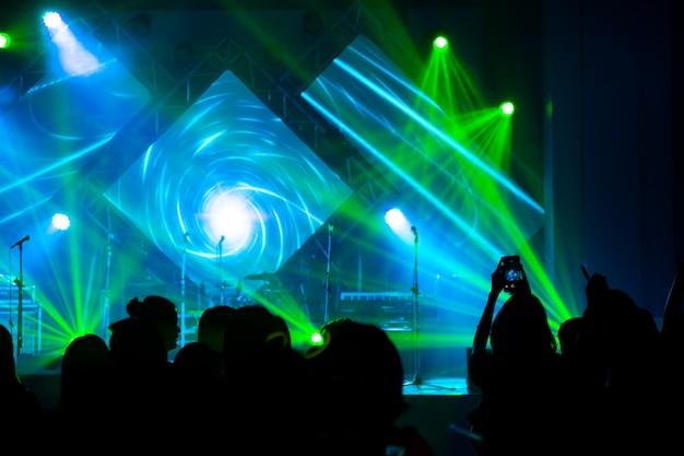 Defocused unterhaltungskonzertbeleuchtung auf stadium mit leuteschattenbild