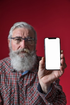 Defocussed älterer mann, der handy mit leerem weißem schirm gegen roten hintergrund zeigt