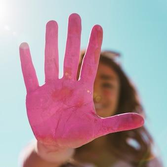 Defocussed junge frau, die im sonnenlicht ihre gemalte rosa holi farbhand gegen blauen himmel zeigt