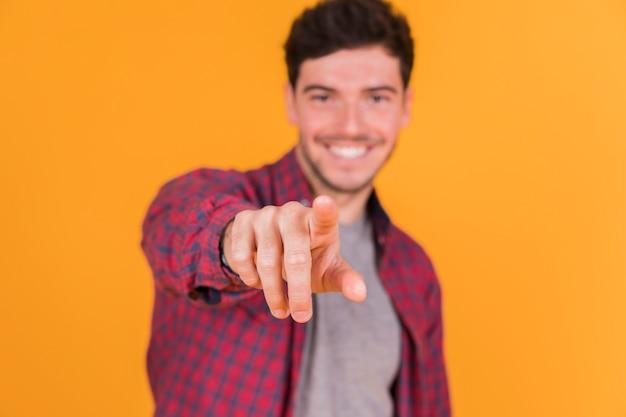 Defocussed junger mann, der seinen finger in richtung zur kamera gegen farbigen hintergrund zeigt